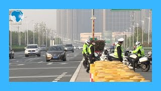 People in cars pass through a road checkpoint in Wuhan as Chinese