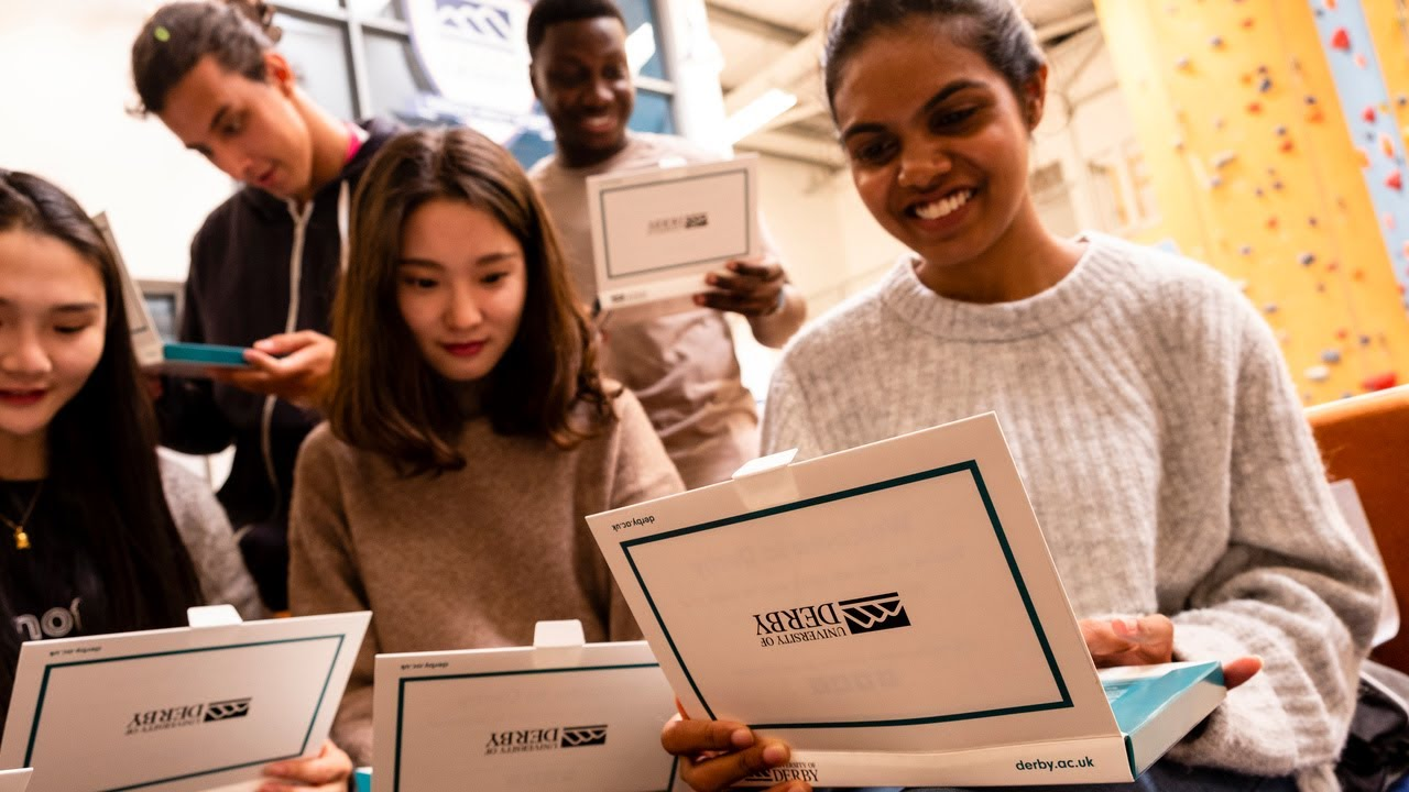 A group of international students opening a University of Derby branded box