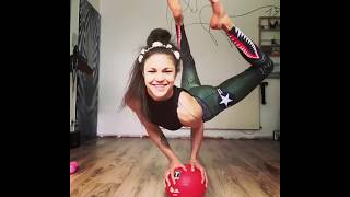 A girl puts glasses on with legs while standing on a ball with hands