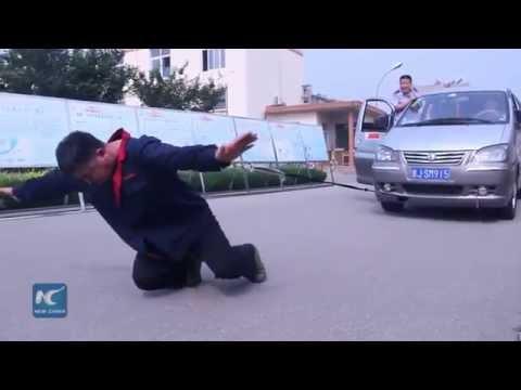 صيني يسير بحذاء وزنه 300 كيلو جرام ويسحب سيارة برقبته!