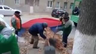 Смотреть онлайн В Волгограде рабочие во флаг России убирают листья