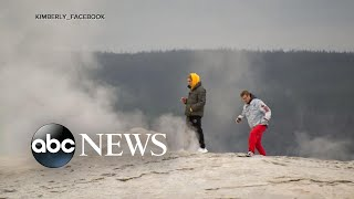 Men stick heads in Old Faithful geyser