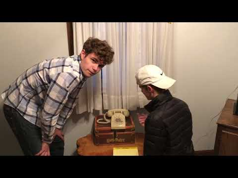 Two teenagers attempt to dial a phone number with a rotary phone