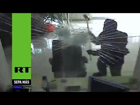 Un ladrón rompe la ventana de un banco con un martillo para entrar a robar