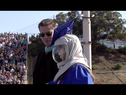 Riley McCoy steps out into the sun for the first time to graduate