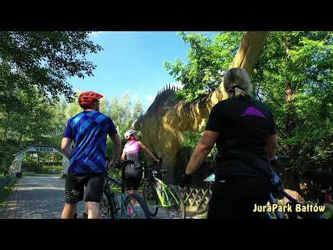 """Trójka rowerzystów spogląda w górę, na ogromnego dinozaura pomiędzy drzewami. Film promocyjny pod tytułem """"Szlakiem przygody – świętokrzyskie dla dzieci"""""""