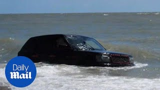 Range Rover swamped by tide and faces being washed into sea