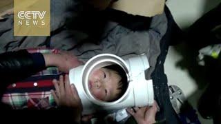 Naughty boy gets head stuck in plastic water pipe