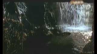 Woman disappears behind waterfall