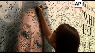 Fans of singer Whitney Houston write condolences on a tribute wall