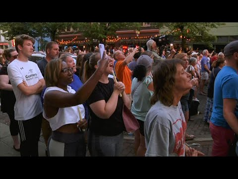 Hundreds crowded into a street in Dayton, Ohio, to hold a vigil for the nine people killed by a gunman early Sunday. Some in the crowd shouted