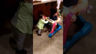 Baby pushes a little girl of two years in a walker