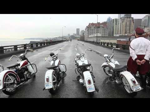 Motorcycle stunt team performs on viaduct