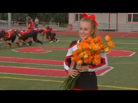 Football players surprise cheerleader battling cancer