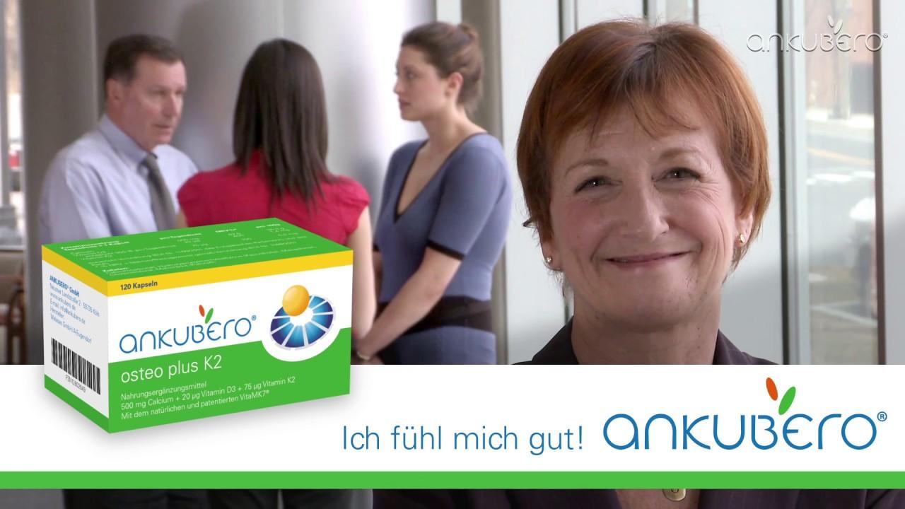 Video-Thumbnail von Produktvideo: lächelnde ältere Frau im Büro mit drei Kollegen im Hintergrund, darüber Packshot 'osteo plus K2' mit Ankubero-Logo und Claim 'Ich fühl' mich gut'