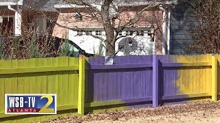 Fence fight: Woman paints fence neon colors after neighbor complains to county