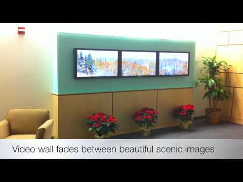 Video of a video wall set up in a 3 x 1 configuration to show panoramic images of scenery. Installed in a hospital's foyer it provides a serene place for visitors to sit and relax. This digital signage display is located next to a two story tall waterfall that provides a babbling brook sound to enhance the effect
