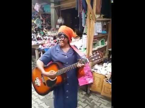 Woman singing and playing guitar in the marketplace