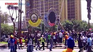 Youths take down President Kenyatta's poster at the GPO roundabout and take it to Uhuru Park grounds