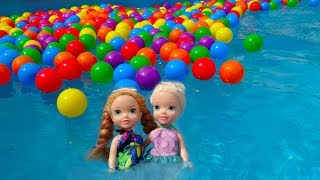 Elsa and Anna toddlers play in the swimming pool