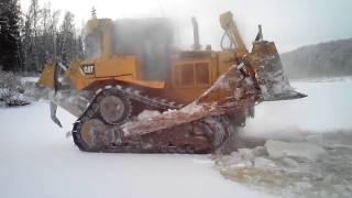 бульдозер ломает лед на реке
