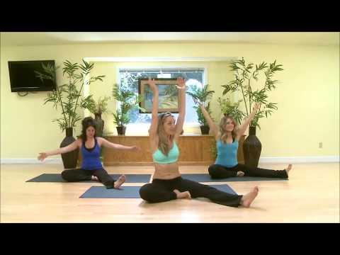 3 women sit on yoga mats working on lower back exerise