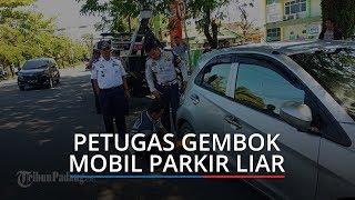 Petugas Gembok Dua Mobil Pelat Hitam yang Parkir di Bahu Jalan di Kota Padang