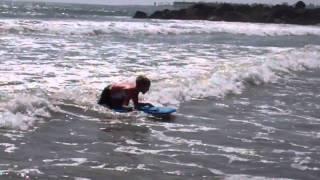 Alex kneeling on boogie board riding a wave