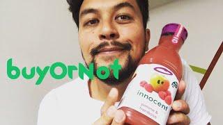 Un jeune homme tient une bouteille de jus de fruit