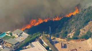 """An explosive fire is threatening multimillion-dollar homes in the hills of Los Angeles. The dry brush on the rugged hillsides is making it very difficult to contain. Jamie Yuccas reports.  Subscribe to the """"CBS Evening News"""" Channel HERE: http://bit.ly/1S7Dhik Watch Full Episodes of the """"CBS Evening News"""" HERE: http://cbsn.ws/23XekKA Watch the latest installment of """"On the Road,"""" only on the """"CBS Evening News,"""" HERE: http://cbsn.ws/23XwqMH Follow """"CBS Evening News"""" on Instagram: http://bit.ly/1T8icTO Like """"CBS Evening News"""" on Facebook HERE: http://on.fb.me/1KxYobb Follow the """"CBS Evening News"""" on Twitter HERE: http://bit.ly/1O3dTTe Follow the """"CBS Evening News"""" on Google+ HERE: http://bit.ly/1Qs0aam  Get your news on the go! Download CBS News mobile apps HERE: http://cbsn.ws/1Xb1WC8  Get new episodes of shows you love across devices the next day, stream local news live, and watch full seasons of CBS fan favorites anytime, anywhere with CBS All Access. Try it free! http://bit.ly/1OQA29B  --- The """"CBS Evening News"""" premiered as a half-hour broadcast on Sept. 2, 1963. Check local listings for CBS Evening News broadcast times."""