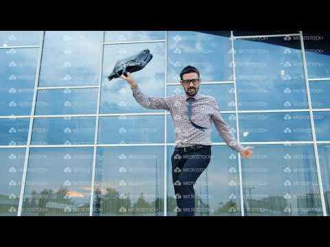 Happy guy in formalwear dancing near office building holding briefcase smiling