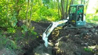 Стрела Бобкэта ныряет в канаву и выныривает с жидкой грязью в ковше