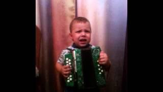 Забавный малыш играет на гармошке и поет