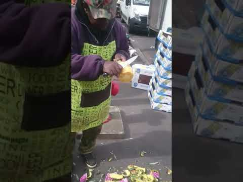 Man at the market peels a pineapple quickly