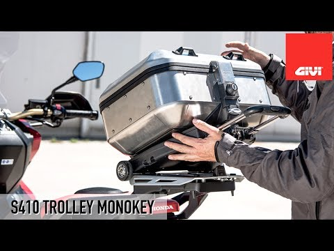 Designed to conveniently turn any GIVI Monokey® top box into a trolley. On the top side the S410 is exactly as any Monokey® mounting plate, so it accepts any top case and flat side case from the Monokey® series. On the flip side the S410 replicates the bottom of any Monokey® case, meaning that the trolley can be attached to any existing Monokey® mounting plate on any motorcycle or scooter. If the motorcycle or scooter have the GIVI optional brake light kit installed, it will not be a problem thanks to the slot featured on the bottom of the S410, that will fit exactly around and over the half of the contact switch, already mounted on the receiving plate. The extendible aluminum handle is light and rugged, and the rubberized grip is designed for extra comfort. It also includes the release button. The wheels are mounted on bearings and are designed to offer the best performance on a variety of surfaces. Thanks to 6 built in strap loops, the trolley can also be used to carry soft bags or small packages.