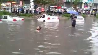 Foreigner swimming on the road when a heavy rain pours water on the street.