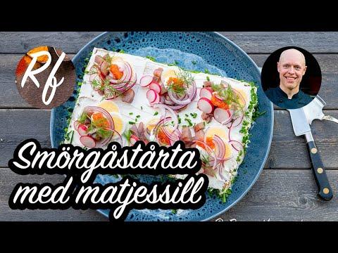 Smörgåstårta med matjessill samt krämig fyllning av Västerbottenost, ägg, dill varvad med kavring och toppad med färskost, kokt ägg, matjessill, rädisor, rom, gräddfil, rödlök och dill.>