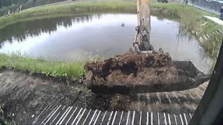 Экскаватор в работе: откосы пруда, планировка, обочины. Excavator at work.