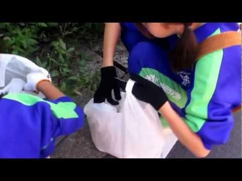 道路のごみを拾う女子中学生。