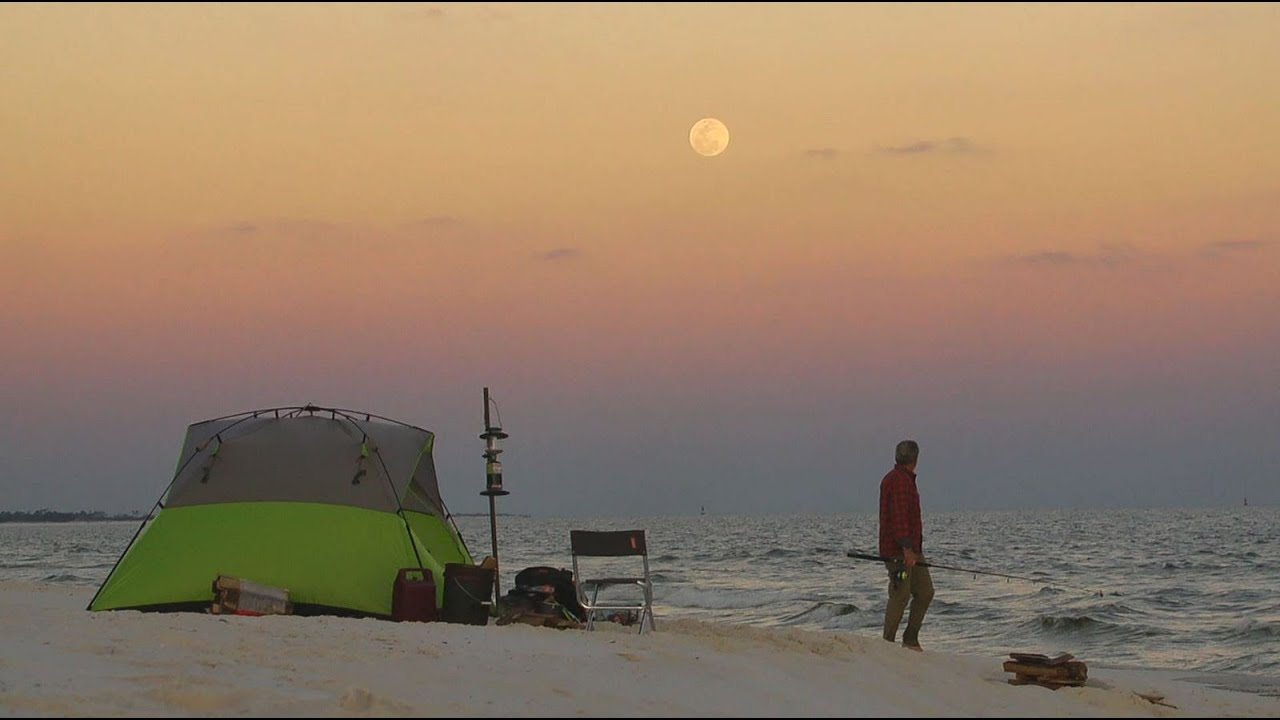 A person camping on the beach in a green  tent and a colorful sky in background