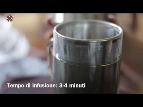 La preparazione del tè verde al gelsomino nella tazza di vetro con infusore
