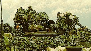 Camouflaged Convoy Of International Battle Tanks And Armored Vehicles Head For The Training Range
