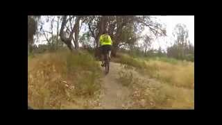 Some guys ride down Olmsted Creek Trail and continue along the outside of Malaga Dunes.