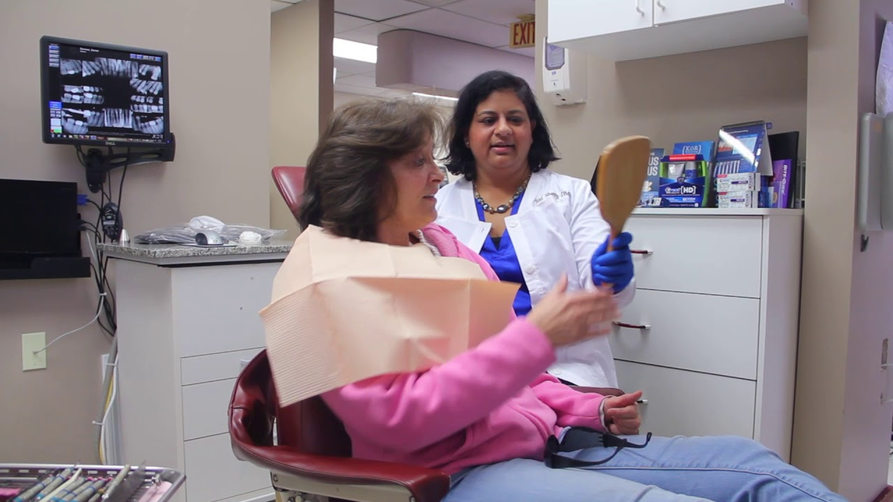 Jini Shetty, DMD showing dental patient results with a mirror