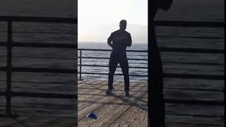 Guy dancing on the pier (by Kate yelkovan)