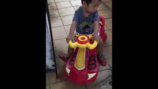 bé chơi xe điện