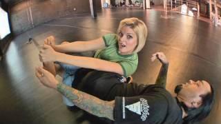 Eddie Bravo shows the Vaporizer leg lock on Joanne of MMA Girls