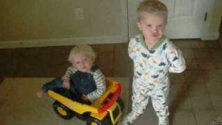 Nathan pushes baby around in tonka, then fights over binky