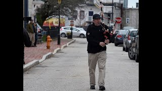 Kris Grills plays a medly of patriotic songs on the bagpipes for neighbors as he walks along Starr Street in New London