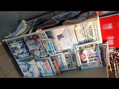Estante con los periódicos del día en una tienda en el aeropuerto de París